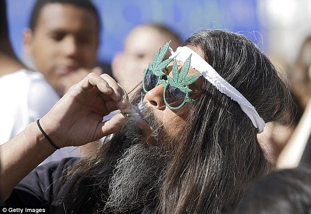 Fast Eddy Aki'a of Hawaii smokes a joint as thousands gather to celebrate Colorado's medicinal marijuana laws in 2012