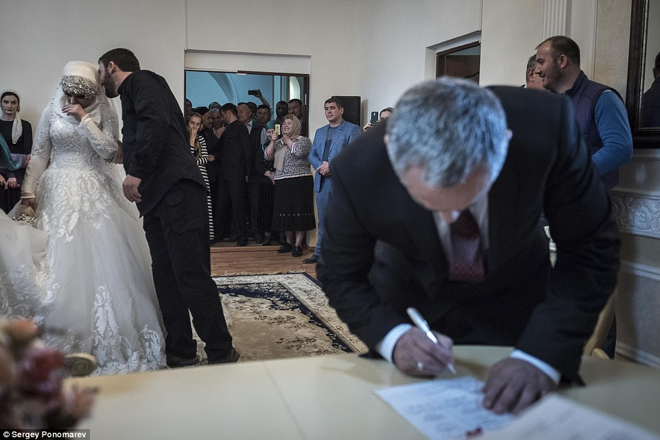 Forlorn: Miss Goilabiyeva appears to weep with sadness as her 47-year-old groom, Chechen police chief Nazhud Guchigov, signs the register