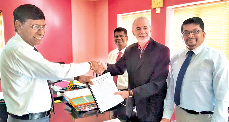 Health Ministry Secretary Dr. Janaka Sugathadasa shaking hands with SCI Country Director Dr. Chris McIvor, while Estate and Urban Health Director Dr. Chulani Gunasekara and SCI Deputy Country Director Julian Chellppah look on.