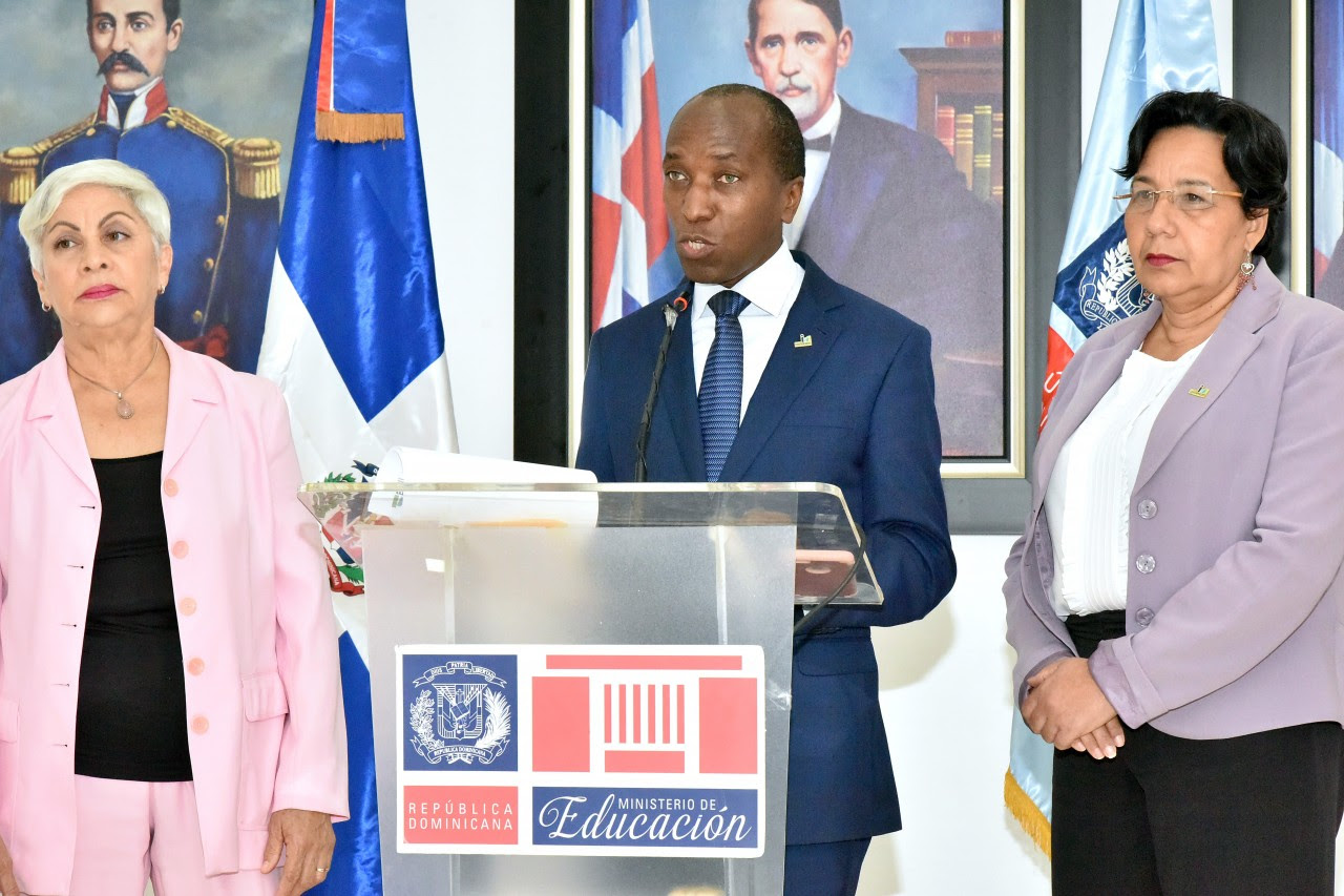 imagen Andrés De Las Mercedes, director ejecutivo del INAFOCAM de pie en podium se dirige a medios de comunicación en rueda de prensa acompañado de dos directivos de dicha institución