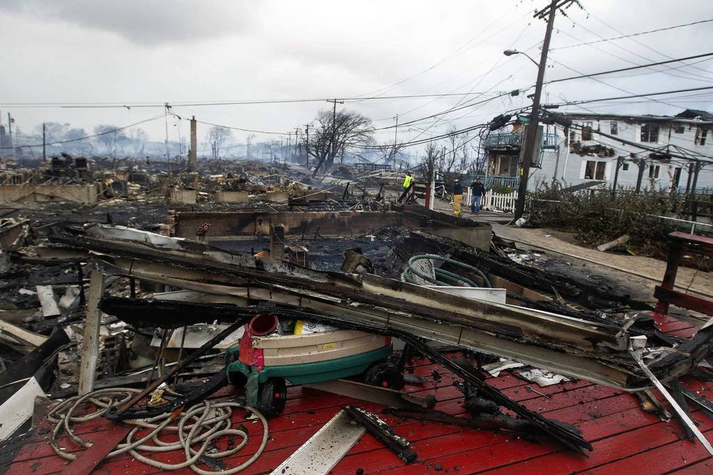 Homes that devastated by fire and the effects of Hurricane Sandy smolder at the Breezy Point section of the Queens borough of New York.