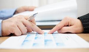 Foto: imagen ilustrativa de la negociación del presupuesto en la que se ven dos manos sobre un papel
