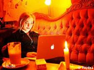 A woman with a laptop surfing the internet in a cafe
