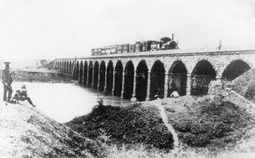 An old picture of one of the first locomotives in India, journeying across the Thane creek.