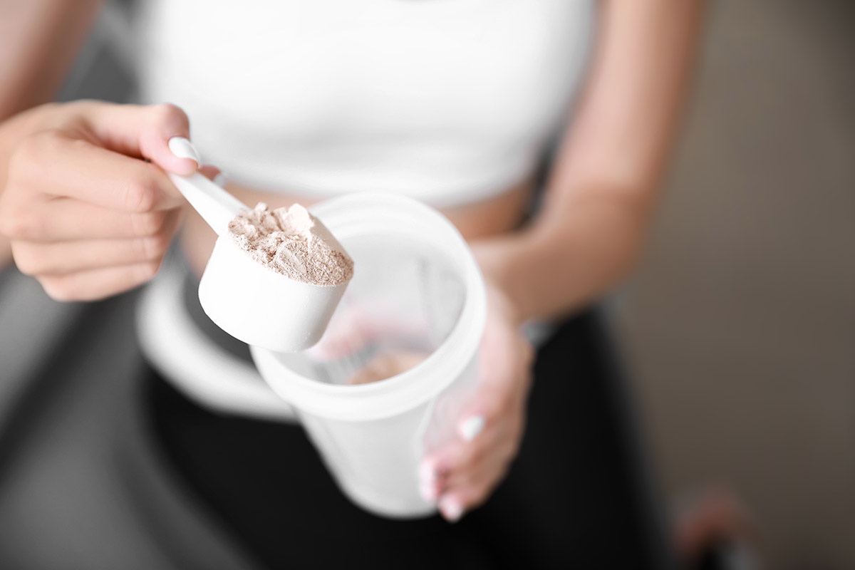 Whey Protein vs. Plant Protein:  Close-up image of protein powder in a scoop