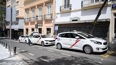 Parada de taxis en la calle de las tiendas con tres vehículos estacionados