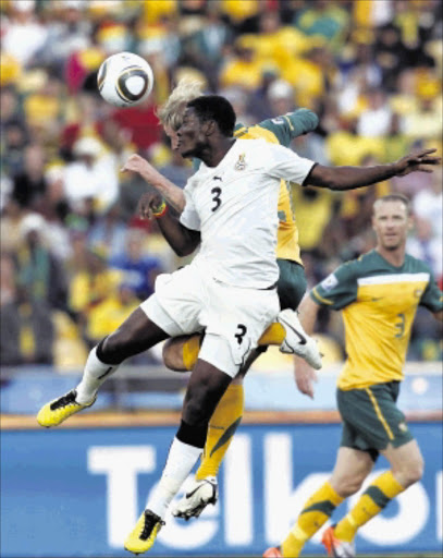 AERIAL DUEL: Asamoah Gyan and David Carney of Australia during the game that ended 1-1 on Saturday. Pic.SIMPHIWE NKWALI. 19/06/2010. © ST. Ghana vs Australia during the group stages of the 2010 FIFA World Cup qualifiers at Rustenburg. Asamoah Gyan(3) and David Carney  during the game. The score is 1-1 at full time  Picture: SIMPHIWE NKWALI/ 19/06/2010