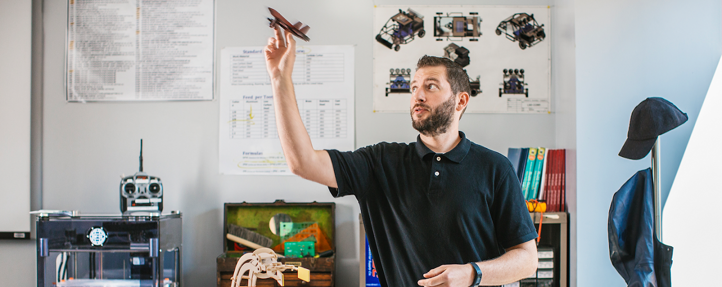 Man tossing a 3-D printed plane. Looks like it was created in the classroom he is in.