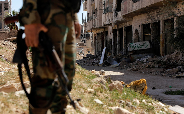 A member of Syrian forces of President Bashar al Assad stands guard in Jobar, eastern Ghouta, in Damascus, Syria April 2, 2018.