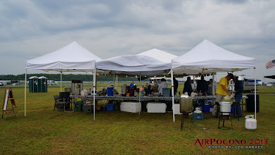 Photo: You're looking at the cooking side of our shelter.  A 3am downpour collapsed the middle pop-up.  Thankfully it was a $50 bargain pop-up and not one of the $150 EZ-ups on either side.  If you're in the market for one the EZ-up's are pretty beefy and that tall center peak takes care of most of the water.  Obie, thank you for your contribution... :-(