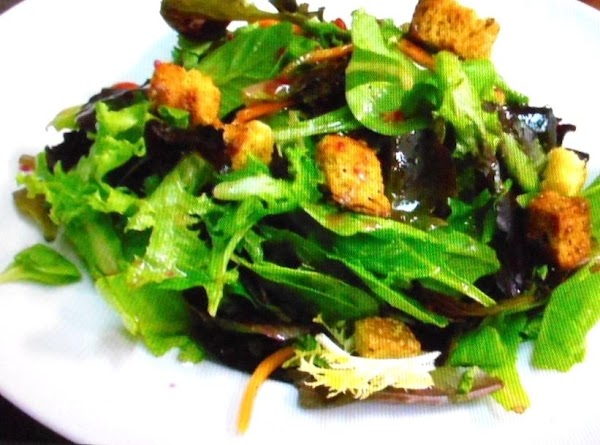 In a large bowl,lightly toss the cleaned greens, with the black olives,the garlic croutons...