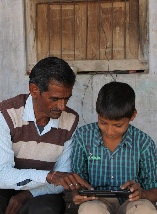 Boy and his father working together on a tablet.