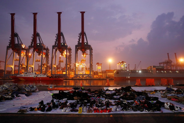 Recovered belongings believed to be from the Indonesian plane crash are laid out at a Jakarta port.