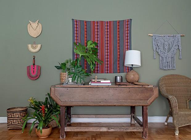Ambiente com mesa de madeira com abajur, livros e vasos em cima, cadeira de palha, piso de madeira, vasos de planta no chão, macramês coloridos na parede verde musgo