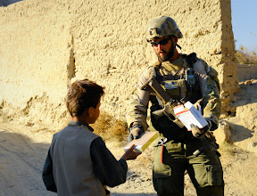 Photo: An International Security Assistance Force Special Operations Forces soldier hands out notepads and pens to an Afghan boy while a Road Maintenance Team checkpoint is being built in Tagab, Afghanistan, Nov. 26, 2010.  Afghan civilians, RMT members, International Security Assistance Force Special Operations Forces and Afghan National Police-Provincial Response Company members all helped to build the checkpoint.   (ISAF photo by U.S. Air Force Staff Sgt. Joseph Swafford/released)