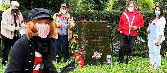 Menschen mit roten Nelken am Gedenkstein.