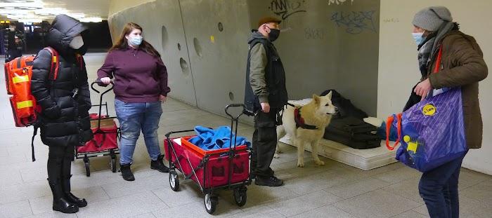 Obdachloser auf Matratze, Helfende mit Bollerwagen, Hund.