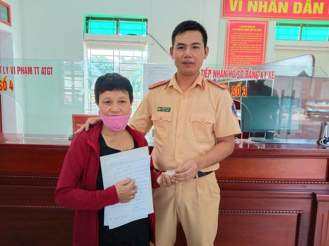 Đồng chí Thượng úy Nguyễn Sỹ Lợi - cán bộ Đội CSGTTT Công an huyện Tân Kỳ trao trả tài sản nhặt được đến chị Trần Thị Dung