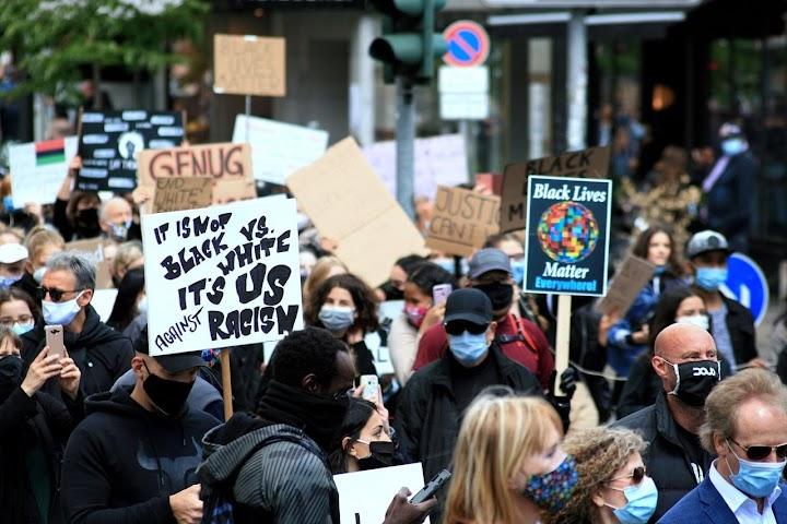 Demonstrierende mit Atemmasken, Schildern.