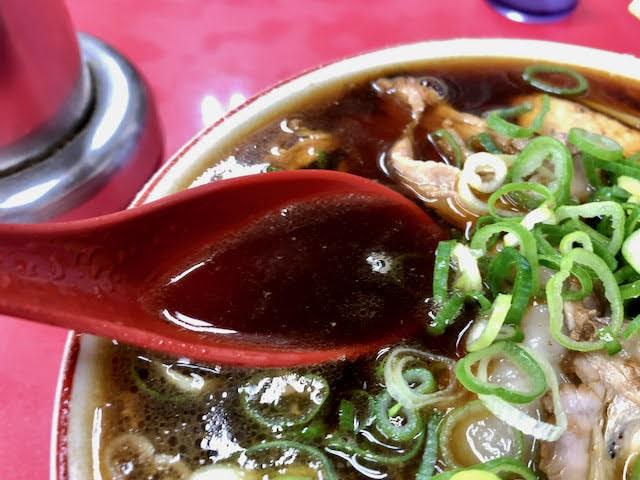 赤いレンゲですくった黒いスープ