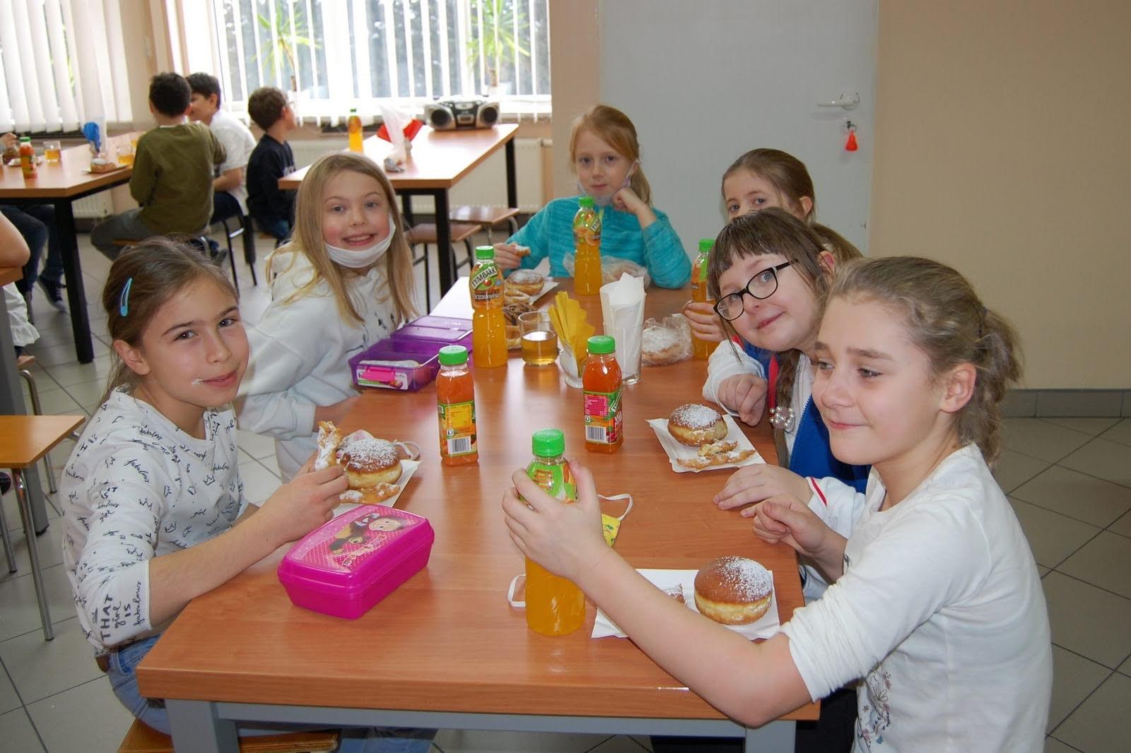 Dzieci jedzące pączki na stołówce szkolnej.
