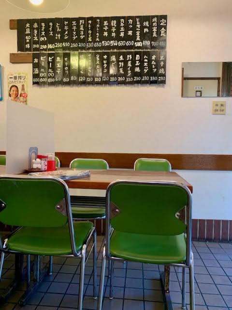 まるけん食堂の店内。テーブル席と壁にかけられた短冊メニュー。