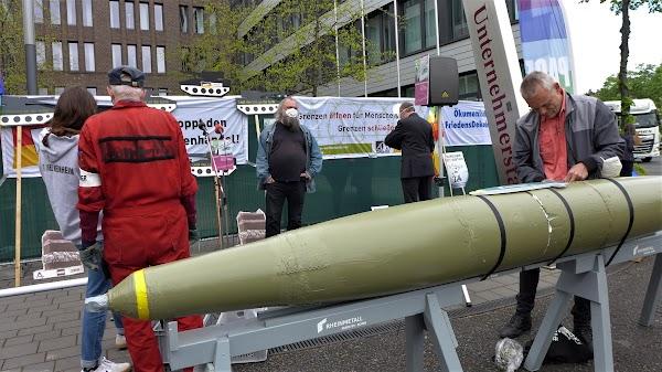Demonstrieende mit Raketenatrappe und Transparenten «Grenzen öffnen für Menschen ...» (verdeckt).