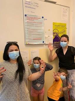 Frauen und Kinder mit Masken.