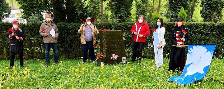 Menschen mit roten Nelken und Friedensfahne am Gedenkstein.