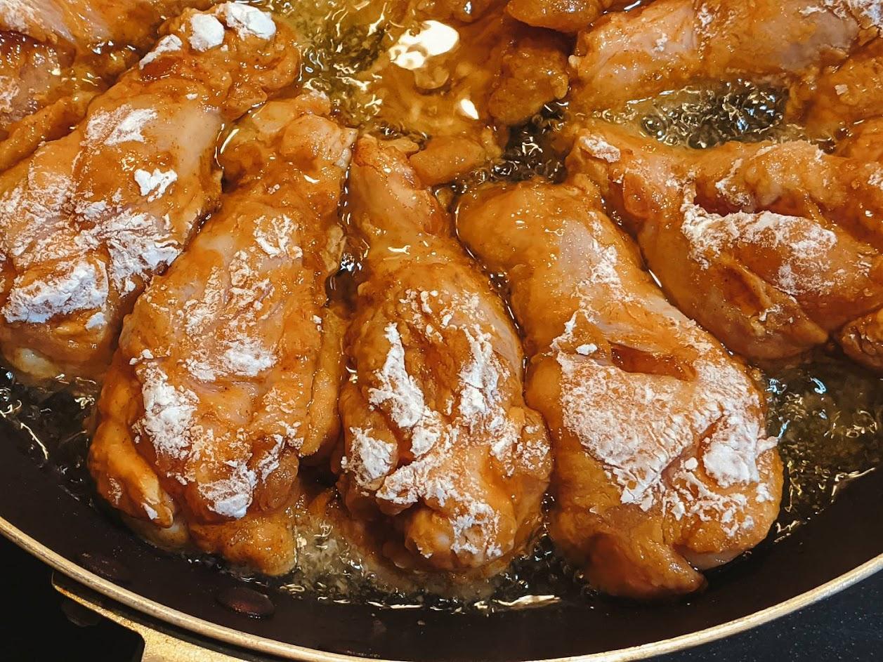 片栗粉をつけた鶏の手羽元を油で揚げている画像