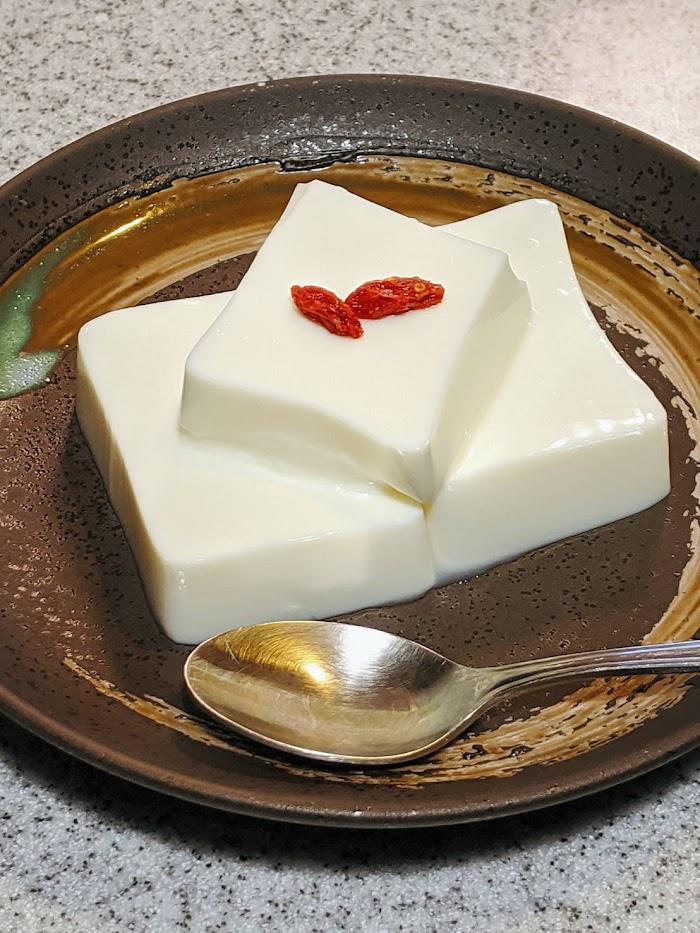 パンダ杏仁豆腐をカットして茶色のお皿に盛りつけた画像