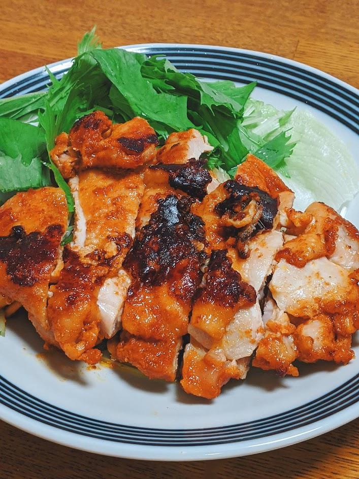 お皿に水菜と一緒に盛りつけたタンドリーチキンの画像