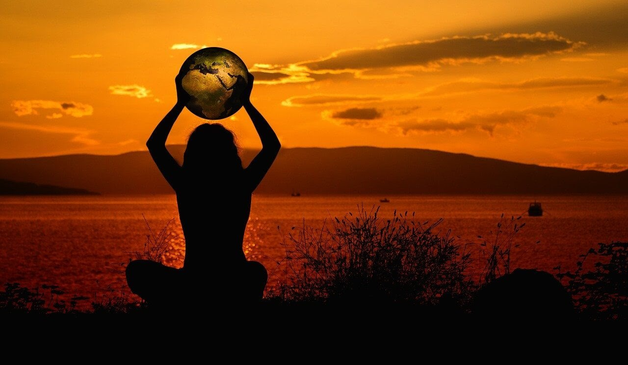 a woman with an earth shaped ball at sunset quotes about life.jpg