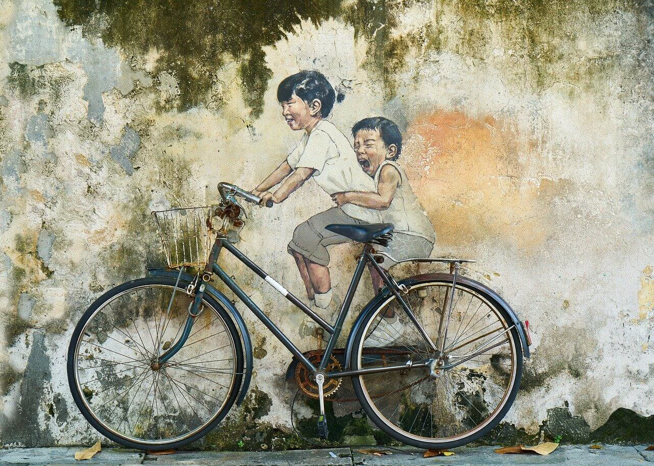 street art in penang boy and girl on cycle used in life quotes to show how simple life could be.jpg