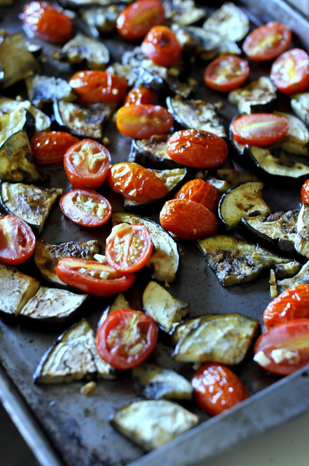 Roast eggplant with grape tomatoes and garlic for a tasty topping for your Friday night pizza.
