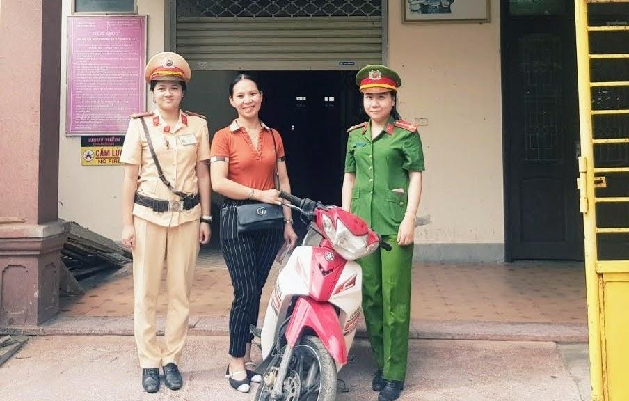 Đại diện Đội Cảnh sát giao thông, trật tự Công an TP Vinh tiến hành trao trả tài sản cho chị Trần Thị Thanh Tú