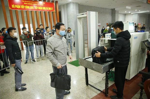 Cựu Bộ trưởng Vũ Huy Hoàng thực hiện kiểm tra an ninh khi vào phòng xét xử. Ảnh: TTXVN