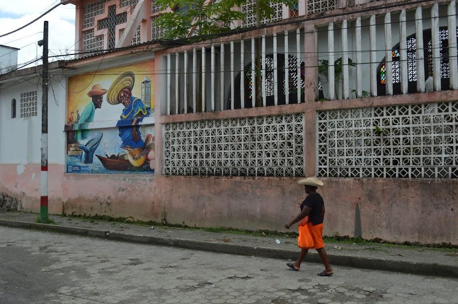 Una mujer afro vestida con falda zapote y sombrero típico camina junto a la catedral de la Inmaculada Concepción, en Guapi, cerca al mural de Oliva Arboleda y Samuelito.