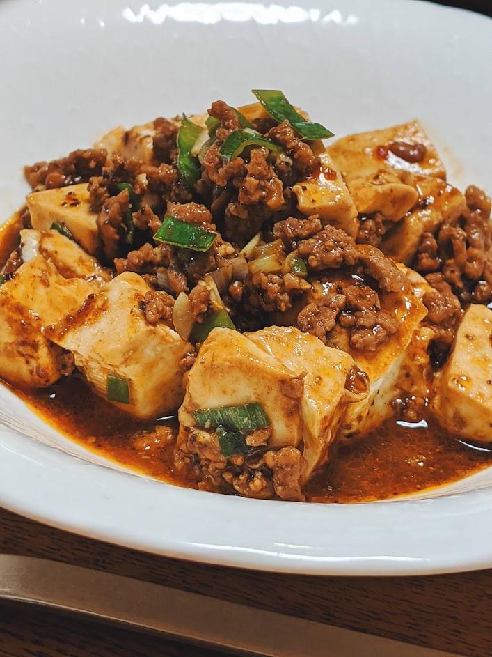 白いお皿に盛りつけた黒麻婆豆腐の画像