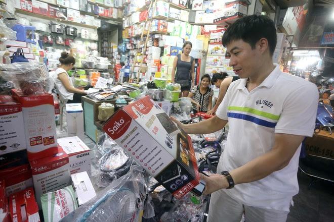 Người tiêu dùng đang lựa chọn bếp từ tại cửa hàng trên phố Hàng Khoai (HN)