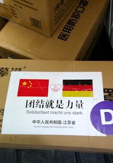 Kartons aus China mit den Fahnen der VR China und der BRD. Beschrifttet: «Solidarität macht uns stark» (in chinesisch und deutsch).