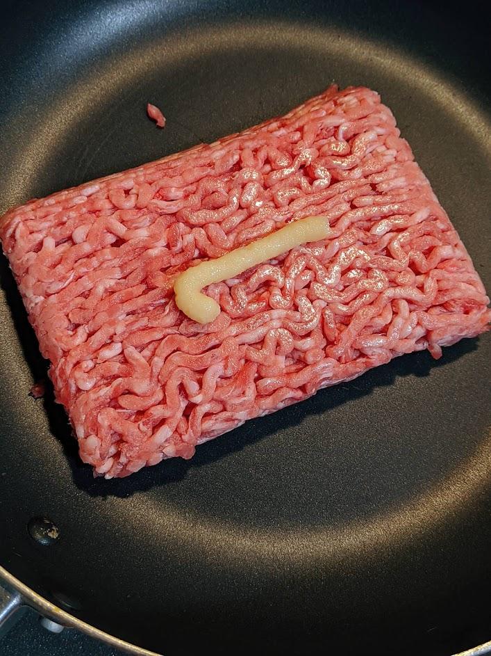 フライパンのひき肉ににんにくチューブを2㎝程度絞り出した画像