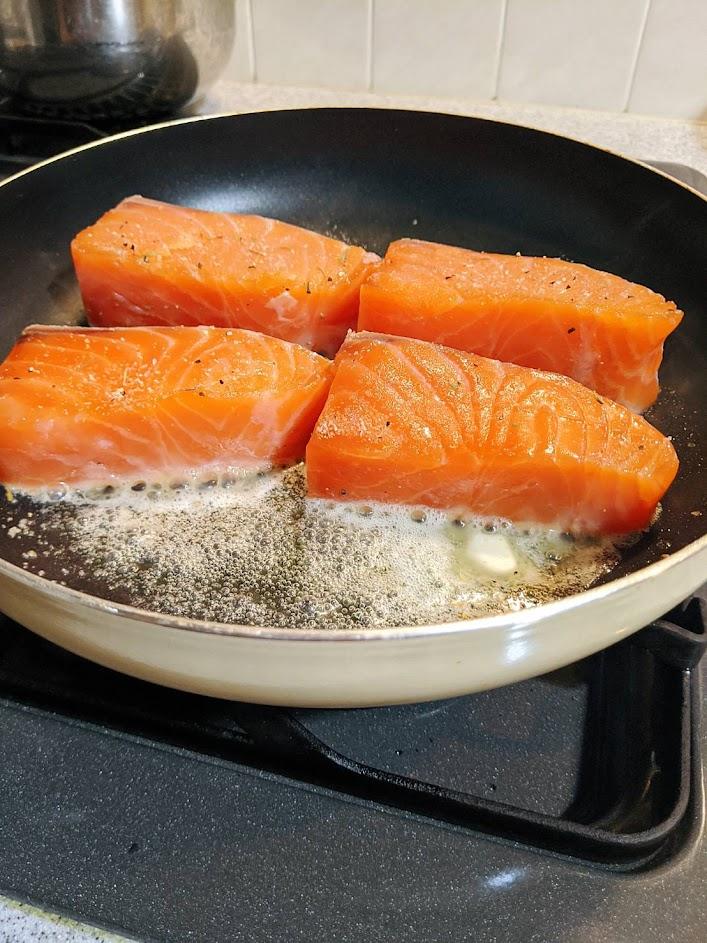 フライパンにバターを入れ、エンペラーサーモンを4切れ入れた画像