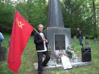 Genosse mit Sowjetfahne am Denkmal.