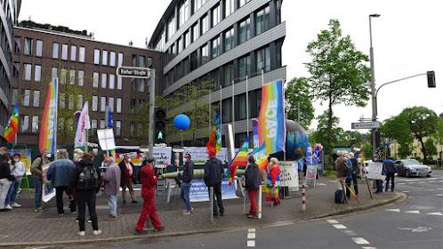 Demonstrierende mit Fahnen und Transparenten vor Gebäudekomplex.