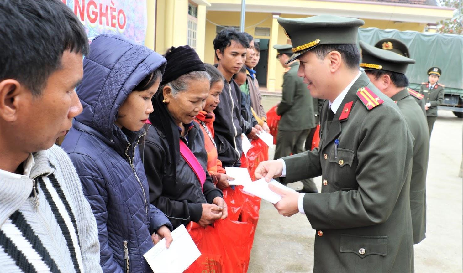 Đồng chí Trung tá Bùi La Sơn, Phó Trưởng Phòng Tham mưu Công an tỉnh trao quà cho bà con nhân dân tại xã Môn Sơn, huyện Con Cuông