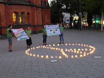 Friedensaktionist:innen mit Friedenszeichen aus Teelichtern vor Kirche.