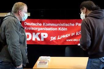 Zwei Genossen mit Mund-Nasenschutz, Transparent «... Kreisorganisation Köln. DKP die Linken in Kölle».
