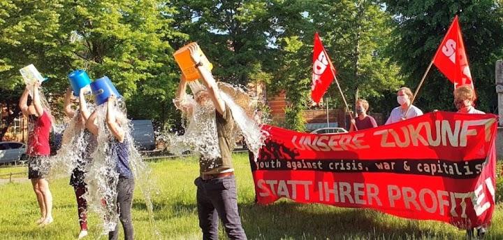 Vier Aktionsteilnehmerinnen leeren einen Wassereimer über sich. SDAJ-Fahnen, Plakat: «Unsere Zukunft statt ihrer Profite!».