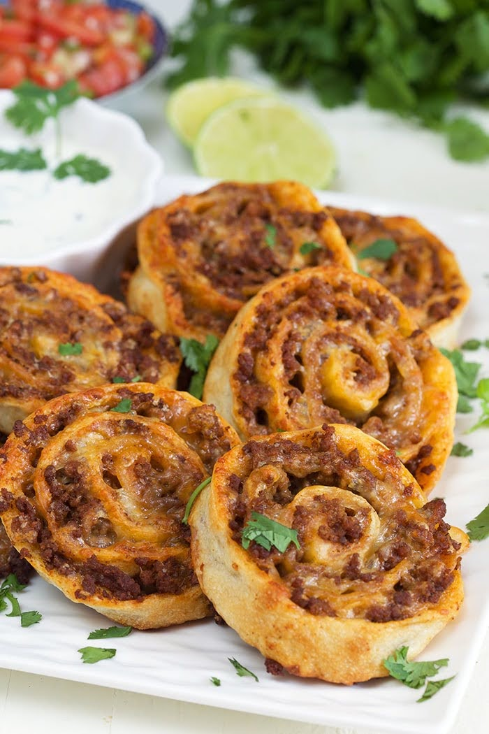 Taco pinwheels on a square white platter with chopped cilantro.
